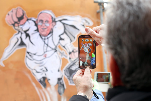"""A man takes a picture with his smartphone of a graffiti featuring a """"superhero"""" version of Pope Francis appears in Borgo Pio, next to St. Peter's Square on January 29, 2014 in Rome, Italy. The image started circulating from the twitter account of the Vatican and has rapidly spread around the world. (Photo by Franco Origlia/Getty Images)"""