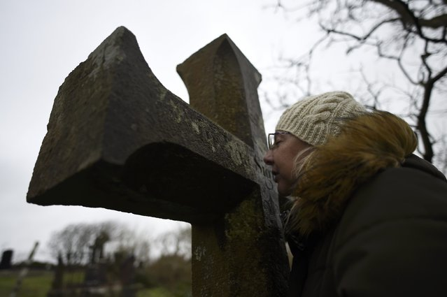 A woman prays at a stone cross during a Pattern Day pilgrimage to St. Brigid at the holy well of St. Brigid in Liscannor, Ireland, February 1, 2017. (Photo by Clodagh Kilcoyne/Reuters)