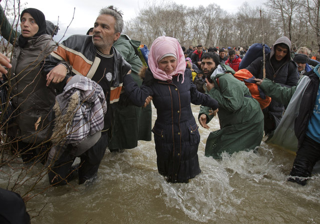 A woman cries as she crosses the river along with other migrants, north of Idomeni, Greece, attempting to reach Macedonia on a route that would bypass the border fence, Monday, March 14, 2016. (Photo by Vadim Ghirda/AP Photo)