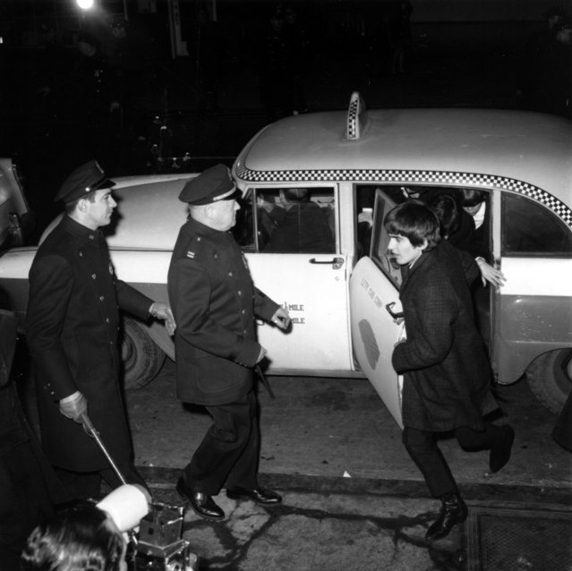 Police security is on hand for the arrival of The Beatles as guitarist George Harrison leads the way from a taxi-cab to Carnegie Hall's stagedoor on W. 56th St. in New York City on February 12, 1964. About 2,000 fans are gathered outside the concert hall to catch a glimpse of the British rock and roll band on their first U.S. tour. (Photo by AP Photo)