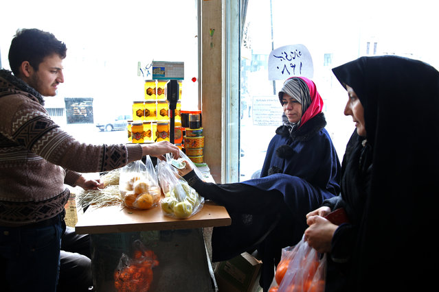 In this picture taken on Wednesday, March 11, 2015, Zohreh Etezadossaltaneh, center, pays for fruit by using her foot to give the cashier money in Tehran, Iran. (Photo by Ebrahim Noroozi/AP Photo)