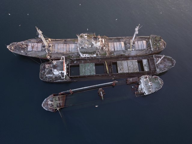 "In this Friday, December 4, 2018 photo, half sunken and abandoned ships are photographed in the Gulf of Elefsina, west of Athens. Dozens of abandoned cargo and passenger ships lie semi-submerged or completely sunken around the Gulf of Elefsina, near Greece's major port of Piraeus. Now authorities are beginning to remove the dilapidated ships. Some of them have been there for decades, leaking hazards like oil into the environment and creating a danger to modern shipping. One expert calls the abandoned ships ""an environmental bomb"". (Photo by Thanassis Stavrakis/AP Photo)"