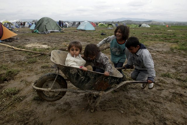 Children play in the mud with a cart at a makeshift camp for refugees and migrants at the Greek-Macedonian border, near the village of Idomeni, Greece March 16, 2016. (Photo by Alexandros Avramidis/Reuters)