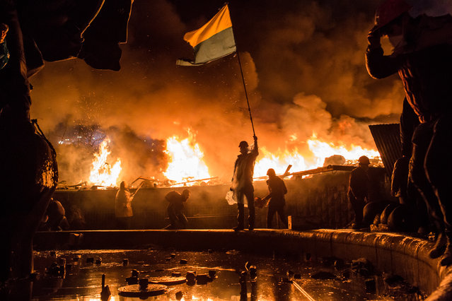 Anti-government protesters guard the perimeter of Independence Square, known as Maidan, on Tuesday in Kiev, Ukraine. Police in Ukraine's capital attacked an opposition camp that's been the center of the massive anti-government protests that began last November. (Photo by Brendan Hoffman/Getty Images)