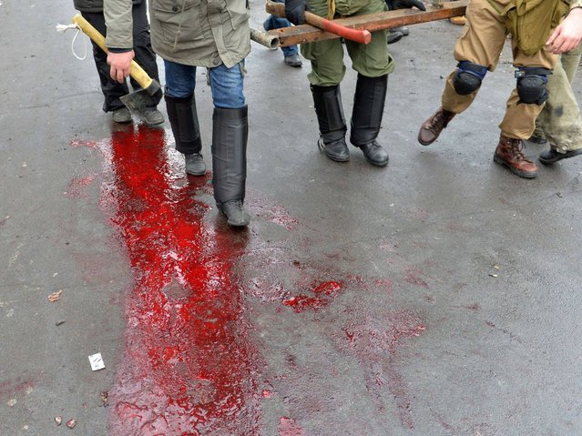Protesters walk on a puddle of blood left by a wounded demonstrator during clashes with the police in the center of Kiev, on February 20, 2014. (Photo by Sergei Supinsky/AFP Photo)