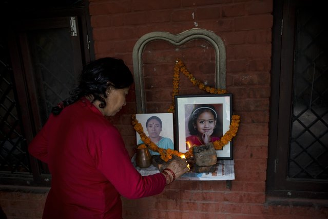 A Nepalese Hindu woman lights a lamp in front of portraits of Chanchala Shreshta, left, and Parbati Shreshta, both victims of last week's earthquake, in Kathmandu, Nepal, Saturday, May 2, 2015. The magnitude-7.8 earthquake killed thousands of people and the U.N. has estimated the quake affected 8.1 million people, more than a fourth of Nepal's population of 27.8 million. (Photo by Bernat Amangue/AP Photo)