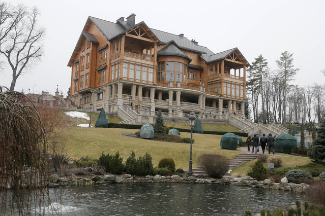 People walk on the territory of Ukrainian President Yanukovych's countryside residence in Mezhyhirya, Kiev's region, Ukraine, Saturday, February 22, 2014. Viktor Yanukovych is not in his official residence of Mezhyhirya, which is about 20 km (12.5 miles) north of the capital. Ukrainian security and volunteers from among Independence Square protesters have joined forces to protect the presidential countryside retreat from vandalism and looting. (Photo by Efrem Lukatsky/AP Photo)
