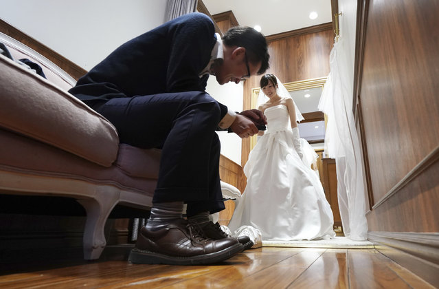 In this April 11, 2019, photo, Kenzo Watanabe smiles as his fiancee Chiharu Yanagihara tries on a wedding dress at a Japanese wedding company in Tokyo. Japan is getting ready for its biggest celebration in years with the advent of the Reiwa era of soon-to-be emperor Naruhito. That means big opportunities for businesses hoping consumers will splash out on long holidays and memorabilia. (Photo by Eugene Hoshiko/AP Photo)