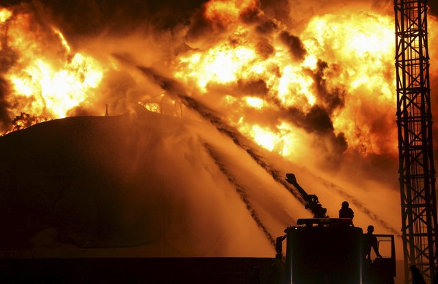 Firefighters try to extinguish a fire at a petrochemical plant in Zhangzhou, Fujian province April 7, 2015. At least six people were injured after an explosion hit part of an oil storage facility on Monday at Dragon Aromatics, Xinhua reported. The fire, which had been put off, resumed at around 7:40 p.m. on Tuesday. (Photo by Reuters/Stringer)
