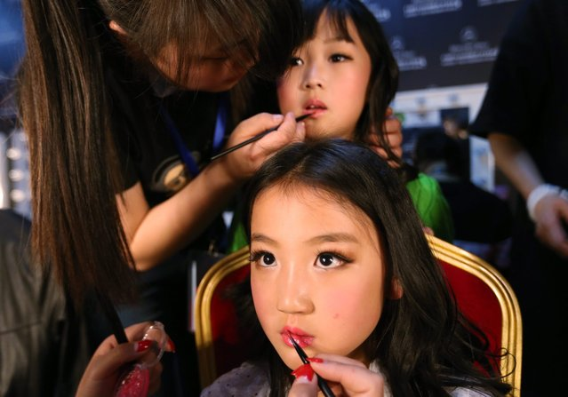 Child models prepare backstage before a fashion show by Chinese designer Vicky Zhang during the Mercedes-Benz China Fashion Week in Beijing, China, 28 March 2016. The fashion week runs until 31 March. (Photo by How Hwee Young/EPA)