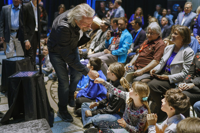 Virgin Galactic founder Richard Branson, gives a fist bump to Sonia Thorp, 9, of Carlos Gilbert Elementary at the beginning of an event at the state capital on Friday, May 10, 2019, in Santa Fe, N.M.  Branson announced Friday that his company will begin shifting operations from California to a spaceport and specialized runway in the New Mexico desert in final preparations for commercial flights. (Photo by Craig Fritz/AP Photo)