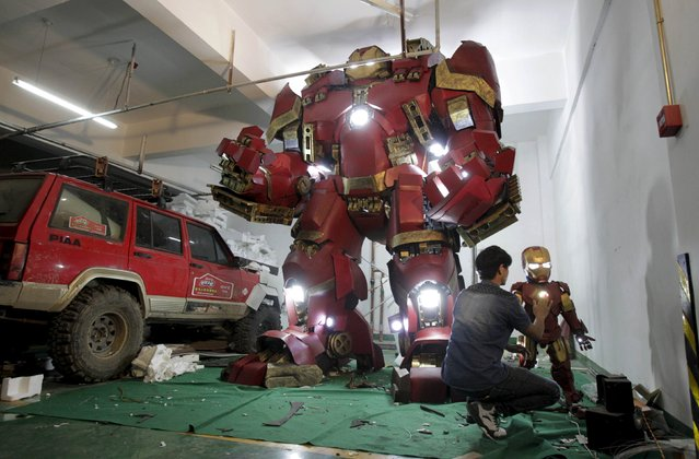 "A man works on a small replica of the Iron Man armor next to a homemade replica of the ""Hulkbuster"" Iron Man armour from the movie ""Avengers: Age of Ultron"", at an underground parking lot in Zhengzhou, Henan province, China, May 12, 2015. (Photo by Reuters/Stringer)"