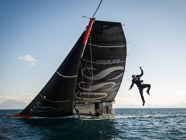 British sailor Alex Thomson performs a stunt involving jumping from his boat. (Photo by Hugo Boss)