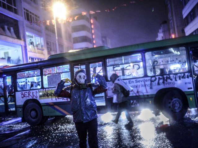 A protester wearing a gas mask stands in front of an empty bus during clashes with riot police in Istanbul. (Photo by Bulent Kilic/AFP Photo)
