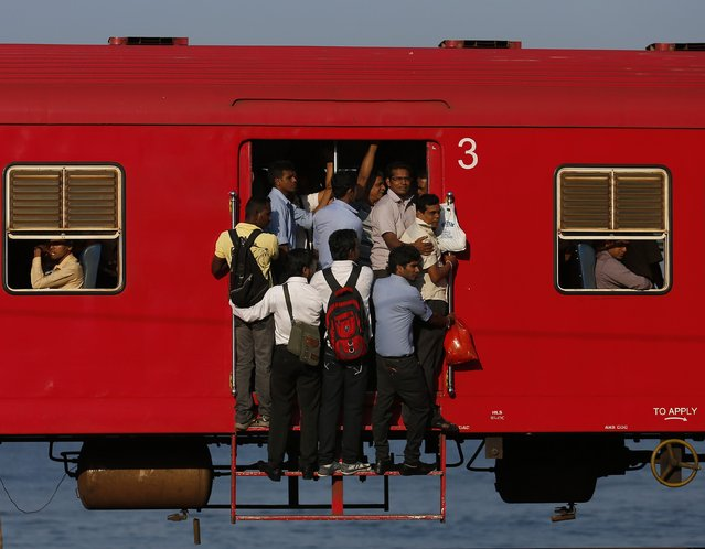 People hang onto a crowded local passenger train as they travel to Colombo March 11, 2014. (Photo by Dinuka Liyanawatte/Reuters)