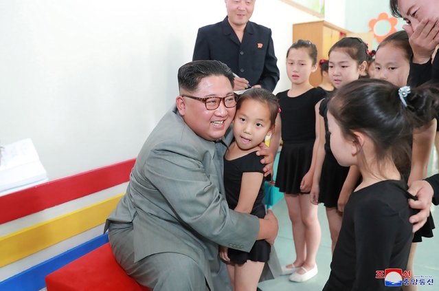 This undated picture released from North Korea's official Korean Central News Agency (KCNA) via KNS on June 1, 2019 shows North Korean leader Kim Jong Un (L) hugging a girl during his visit to the 250-mile Journey for Learning Schoolchildren's Palace in Jagang province in North Korea. (Photo by KCNA via KNS/AFP Photo)