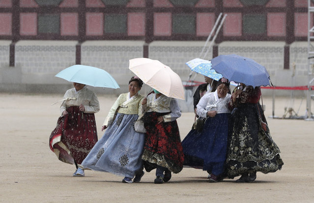 """In this April 25, 2019, file photo, visitors dressed in South Korean traditional """"Hanbok"""" attire put up umbrellas at the Gyeongbok Palace, the main royal palace during the Joseon Dynasty, and one of South Korea's well-known landmarks in Seoul, South Korea. (Photo by Lee Jin-man/AP Photo/File)"""