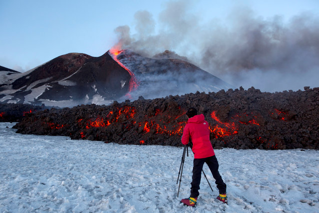 A tourist stands in front of Italy's Mount Etna as it spews lava during an eruption on the southern island of Sicily, Italy on March 1, 2017. (Photo by Antonio Parrinello/Reuters)