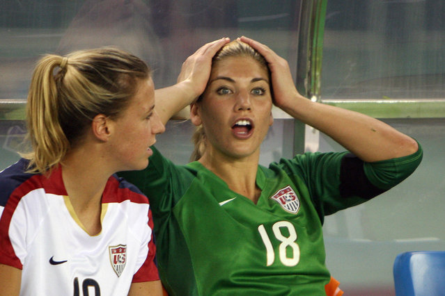 Replaced US goalkeeper Hope Solo (R) sits on the bench with teammate Aly Wagner (L) before losing their 2007 FIFA Women's World Cup football tournament semi-final match 4-0 to Brazil at the Dragon Stadium in Hangzhou, 27 September 2007. Solo was replaced by veteran US goalkeeper Briana Scurry in the lead up to the game. (Photo by Mark Ralston/AFP Photo)