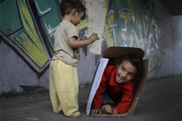 Yara, 5, and her brother Youssef, left, 16 months, hide inside a cardboard box as they play under a bridge while their mother sells tissue in Cairo, Egypt, Thursday, May 14, 2015. (Photo by Hassan Ammar/AP Photo)