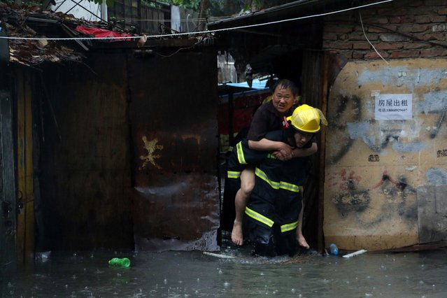 Rescuers helping a resident through a flooded area during an intense rainstorm that killed 7 people in Xiamen, east China's Fujian province. Rainstorms have lashed large swathes of south and central China since May 17, affecting more than a million and leaving at least 15 dead and seven missing. (Photo by AFP Photo/Stringer)