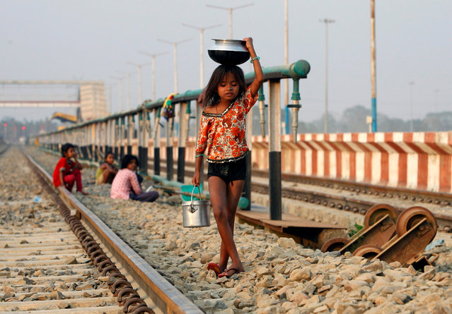 A girl carries utensils after filling them with water from a pipe that supplies water to trains at a railway station on the outskirts of Agartala, India, February 28, 2017. (Photo by Jayanta Dey/Reuters)