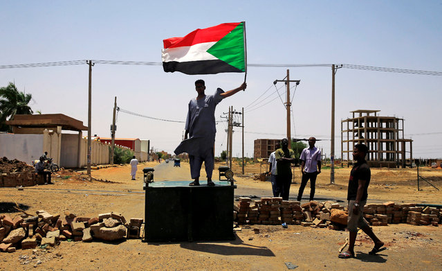 A Sudanese protester holds a national flag as he stands on a barricade along a street, demanding that the country's Transitional Military Council hand over power to civilians, in Khartoum, Sudan June 5, 2019. (Photo by Reuters/Stringer)