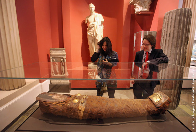 Members of the public view a mummy of a young woman from during the Roman occupation of Egypt in the Ashmolean Museum