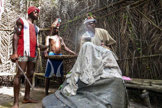 Chief Baykuh, a traditional healer performs a ceremony on a young Abu Koroma who has been shot with a witch gun in Magbumoh on December 1, 2018. In traditional culture. a witch gun is a spell or curse placed on a individual causing physical or mental illness. In order to be treated, the Chief covers his patient with a blanket and places a boiling pot of medicine beneath him to be evaporated into his body. The ceremony concludes with Baykuh blowing a spiritual powder overtop Abu's head. (Photo by Lynn Rossi/AFP Photo)