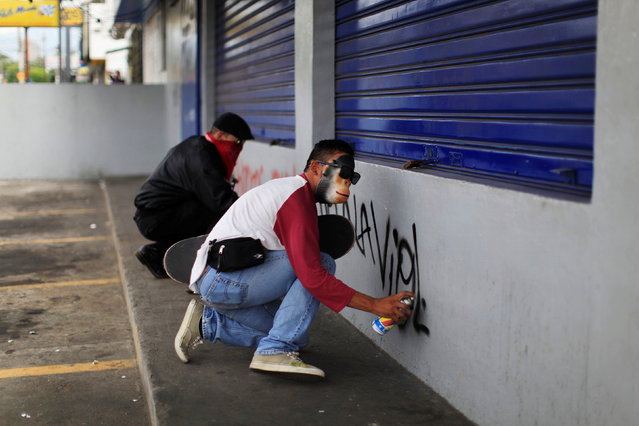 A demonstrator spray paints graffiti on a wall during the May Day march in San Salvador, El Salvador May 1, 2016. (Photo by Jose Cabezas/Reuters)