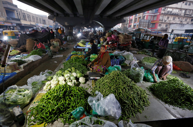 Vendors selling vegetables wait for customers under a flyover in the early morning in Ahmedabad, February 1, 2017. (Photo by Amit Dave/Reuters)