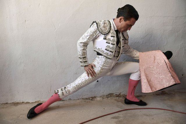 "Spanish bullfighter Octavio Chacon warms up before entering the bullring at the San Fermin Festival in Pamplona, northern Spain, Sunday, July 14, 2018. Revelers from around the world flock to Pamplona every year to take part in the eight days of the running of the bulls, and say good bye today with the sing ""Pobre de Mi"" in the midnight. (Photo by Alvaro Barrientos/AP Photo)"