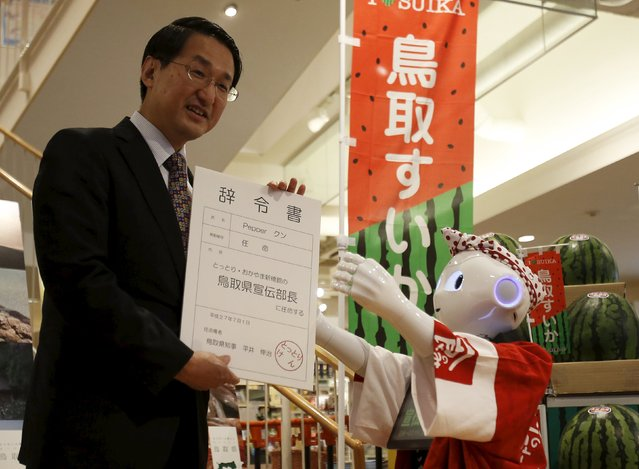 "SoftBank's human-like robot named ""Pepper"" receives an appointment letter as a PR manager of Tottori prefecture from Shinji Hirai, the prefectural governor, at the prefecture speciality store in Tokyo, Japan, July 1, 2015. (Photo by Yuya Shino/Reuters)"