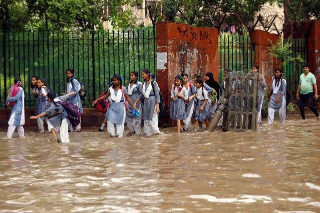 School girls wade through a waterlogged street after heavy rains in New Delhi, India, August 6, 2019. (Photo by Anushree Fadnavis/Reuters)