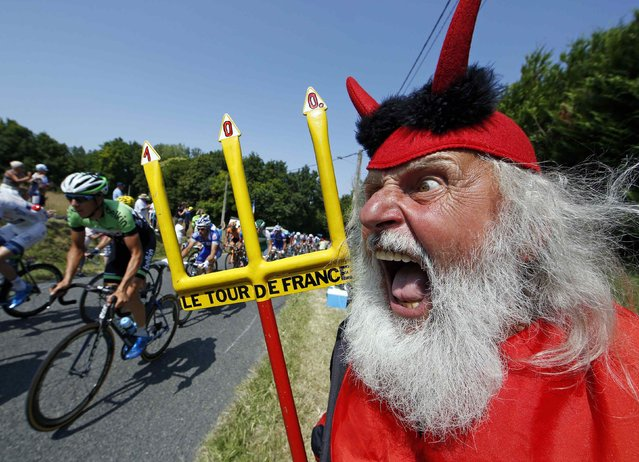 "The pack of riders makes its way past Didi Senft, a cycling enthusiast better known as ""El Diablo"" (The Devil), during the twelfth 218km stage of the centenary Tour de France cycling race from Fougeres to Tours July 11, 2013. (Photo by Eric Gaillard/Reuters)"