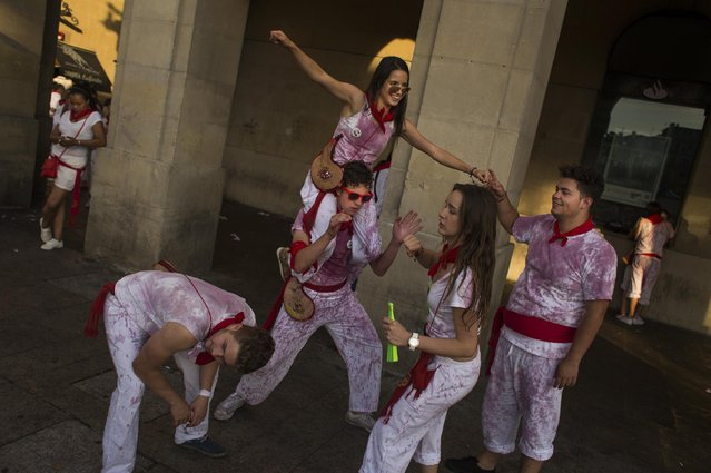 Revelers dance with their clothes covered in wine during the San Fermin festival, in Pamplona, Spain, Tuesday, July 7, 2015. (Photo by Andres Kudacki/AP Photo)