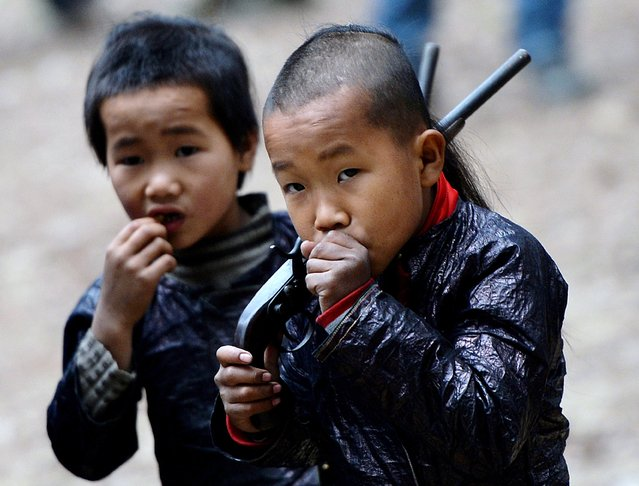 This photo taken on February 4, 2014 shows young members of the Miao minority group carrying replica guns in Biasha Village, Guizhou Province. The armaments in Biasha, a village tucked amid the wooded peaks of Guizhou province, are a reminder of an era of conflict between Beijing and the mountain tribes who still inhabit swathes of China's southwest. (Photo by Mark Ralston/AFP Photo)