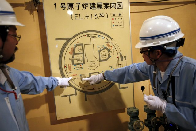 An employee of Kyushu Electric Power Co. (R) speaks to reporters inside the No.1 reactor building where fuel rods are being inserted into a reactor vessel at Sendai nuclear power station in Satsumasendai, Kagoshima prefecture, Japan, July 8, 2015. (Photo by Issei Kato/Reuters)