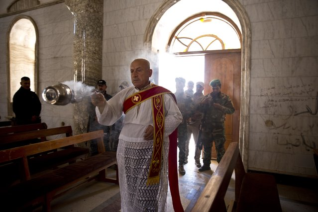 Christian militiamen stand guard during Easter mass in Qaraqosh, outside Mosul, Iraq, Sunday, April 16 2017. The town has been gutted by Islamic State militants. Now under government control, residents have not returned. (Photo by Maya Alleruzzo/AP Photo)