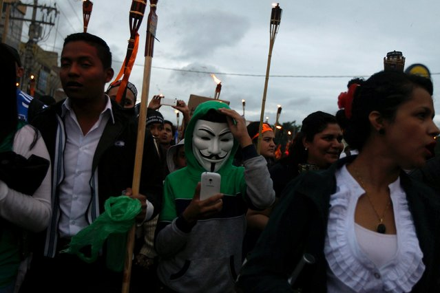 A demonstrator, wearing a Guy Fawkes mask, checks his mobile phone during a march to demand the resignation of Honduras' President Juan Orlando Hernandez in Tegucigalpa, July 10, 2015. (Photo by Jorge Cabrera/Reuters)