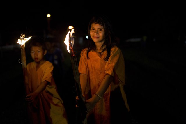 In this June 23, 2015 photo, Ashaninka Indian school children parade with torches during festivities celebrating the 44th anniversary of their village, in Otari Nativo, Pichari, Peru. The village is located in a valley near the Apurimac, Ene and Mantaro rivers in the world's largest coca growing region. (Photo by Rodrigo Abd/AP Photo)