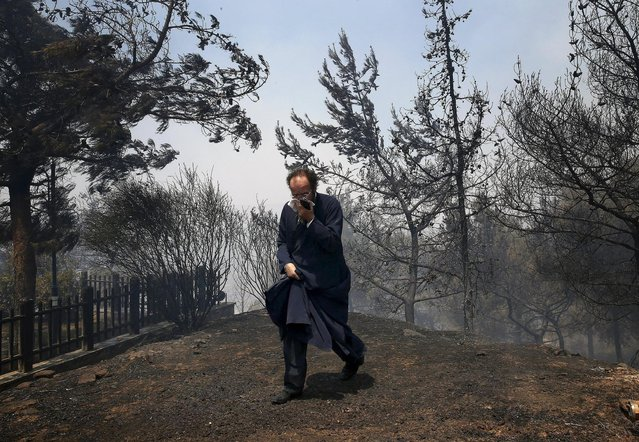 A Greek Orthodox priest covers his nose and mouth as he walks away from a forest fire close to Saint George church in an Athens neighborhood, July 17, 2015. (Photo by Yannis Behrakis/Reuters)