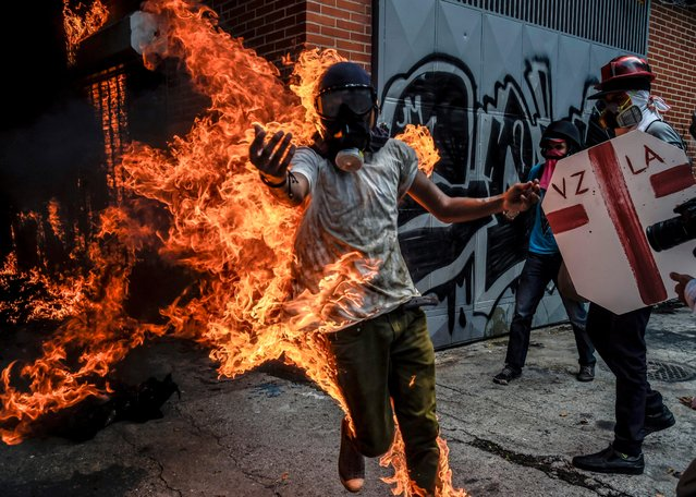 A demonstrator catches fire after the gas tank of a police motorbike exploded during clashes in a protest against Venezuelan President Nicolas Maduro, in Caracas on May 3, 2017. (Photo by Juan Barreto/AFP Photo)