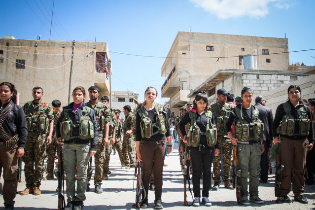 Fighters in the Kurdish militia known as the Popular Protection Units line up in formation in front of supporters in Ras Al Ayn, Syria, on April 14, 2013. (Photo by Danny Gold/NBC News)