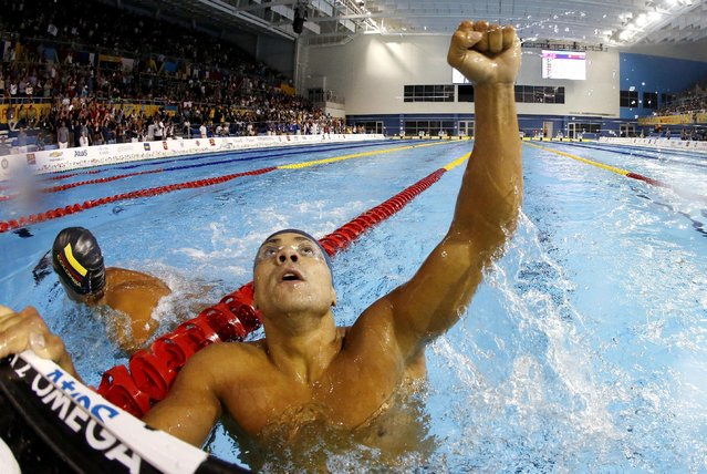 In a photo taken with a fisheye lens, Brazil's Felipe Franca Da Silva celebrates after winning the gold medal in the men's 100m breaststroke final at the Pan Am Games, Friday, July 17, 2015, in Toronto. (Photo by Julio Cortez/AP Photo)