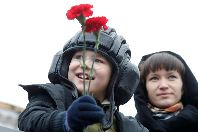 A child holds flowers before the parade during the 72nd anniversary of the end of World War II on the Red Square in Moscow, Russia on May 9, 2017. (Photo by Sergei Karpukhin/Reuters)