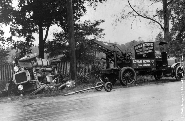 1925: An auto ambulance (right) beside a crashed car on a road in England. The auto-ambulance lifted the car so that the drivers and passengers could be rescued