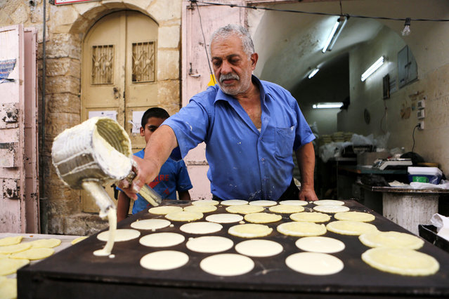 A Palestinian candy vendor makes a traditional special sweet for the month of Ramadan, at his shop in the West Bank city of Hebron, 05 June 2016. (Photo by Abed Al Hashlamoun/EPA)