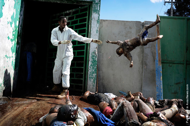 A man throwing the body of a dead child at the morgue of the general hospital, Port-au-Prince
