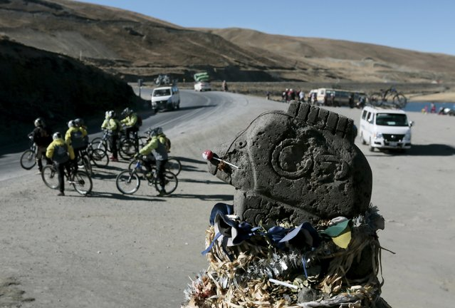 "Cyclists are seen next to a condor staute at ""La Cumbre"" near La Paz, August 1, 2015. (Photo by David Mercado/Reuters)"